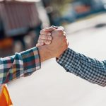 Close-up_of_two_workers_giving_a_handshake_
