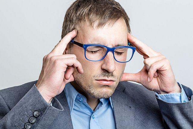 Mann im Stress mit Kopfschmerzen
