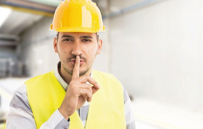 Factory_or_company_engineer_making_shush_silence_gesture_with_index_finger_on_lips
