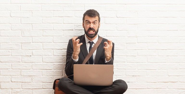 Businessman_with_his_laptop_sitting_on_the_floor_annoyed_angry_in_furious_gesture