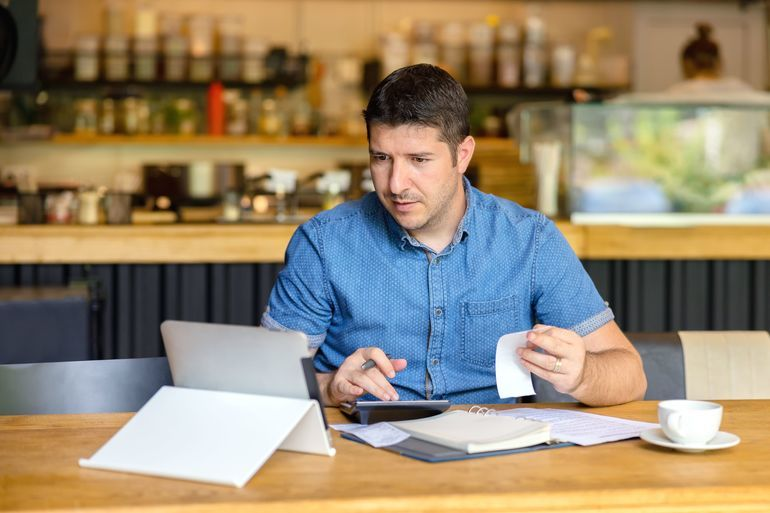Mature_small_business_owner_calculating_finance_bills_of_activity_–_Entrepreneur_using_laptop_and_calculator_to_work_and_to_calculate_and_analyze_financial_expenses_of_new_business_start-up