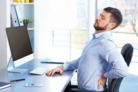 Posture_concept._Man_suffering_from_back_pain_while_working_with_computer_at_office