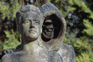 Death_skeleton_statue_symbol_tombstone_in_the_cemetery.