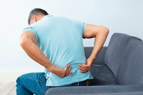 Mature_Man_Sitting_On_Sofa_Suffering_From_Back_Pain