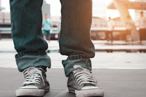 close_up_legs_men_casual_wearing_jeans_and_shoes_stand_on_concrete_stair._waiting,_start__up_and_ready_concept._travel_concept.