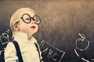 Portrait_Cute_Little_Boy_with_Glasses_Child_Prodigy_Dark_Chalking_Board_Text_Sign_Concept_Back_to_School_Black_Background