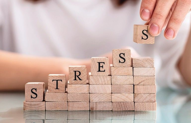 Close-up_Of_Person's_Hand_Placing_Last_Alphabet_Of_Word_Stress_On_Wooden_Block