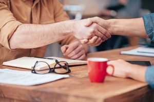 Sealing_a_deal._Close-up_of_two_men_shaking_hands_while_sitting_at_the_wooden_desk_