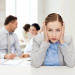 business_and_office_concept_-_stressed_businesswoman_covering_her_ears_with_hands