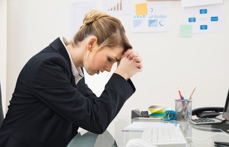 Portrait_Of_Upset_Young_Businesswoman_Sitting_At_Desk_In_Office