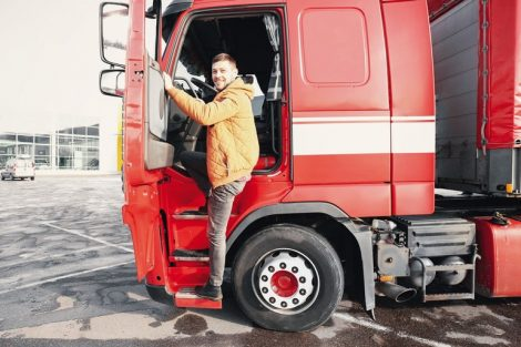 Handsome_driver_near_big_modern_truck_outdoors