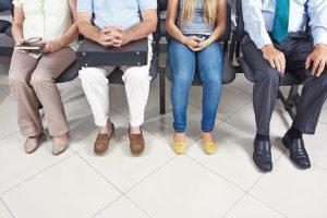 Füße_von_verschiedenen_wartenden_Leuten_im_Wartezimmer