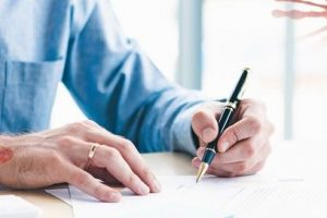 Work_from_home._Prevention_of_Coronavirus_infection_or_COVID-19_on_white_background_concept._Close_up_businessman_hand_signing_contract_paper_on_document_finance._Panoramic_banner_with_copy_space.