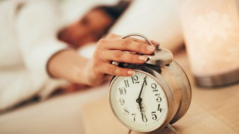 Beautiful_young_woman_sleeping_in_bed_and_holding_hand_on_alarm_clock._Selective_focus._Focus_on_foreground,_on_clock.