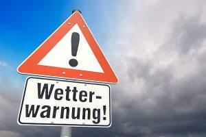 Ein Schild warnt vor Unwetter