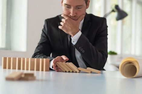 Worried_serious_businessman_sitting_at_his_desk_stopping_domino_effect_with_his_hand_as_he_plans_the_future_of_his_company.