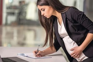 Pregnant_adult_businesswoman_working__at_her_working_place_in_office.