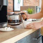 Beautiful_woman_using_coffee_machine_in_kitchen
